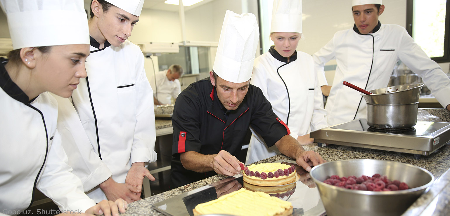 Four student chefs watching a teacher decorate a cake - Does a culinary school train students for jobs as chefs and cooks?